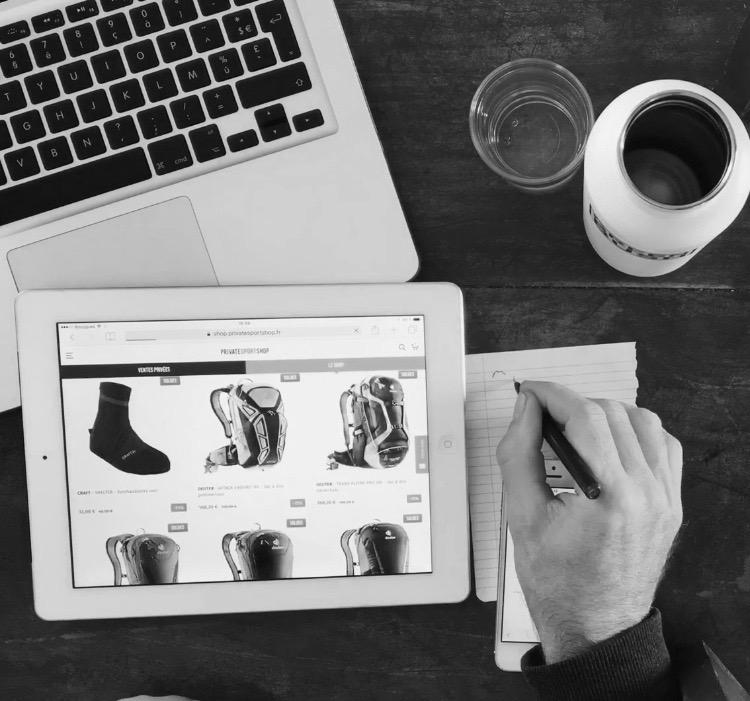 Un homme prend des notes sur un cahier en consultant un site internet